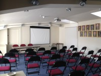 interior of the community room with a projection screen, table & rows of chairs