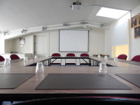 interior of the community room with a projection screen, tables & chairs