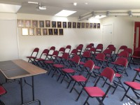 interior of the community room with rows of chairs. Portrait photos of former mayors are on the wall.