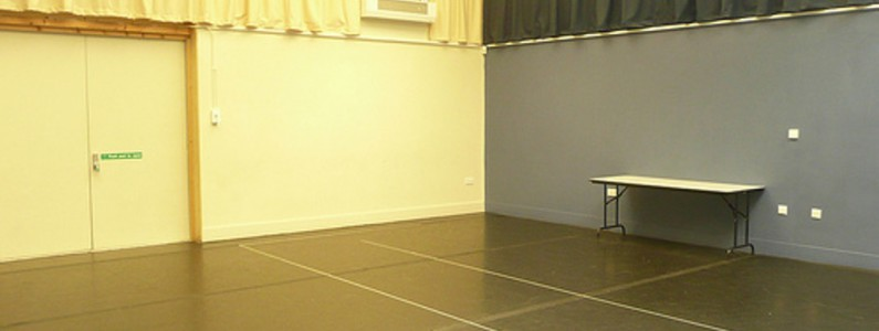interior image of the empty workshop room showing blue & white walls, black flooring & a table