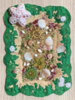 An embroidered beach scene with fabric and shell details