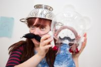 A woman wearing a fake moustache wearing a collinder on her head holds a doll which also has a moustache and has its head inside a clear plastic bowl