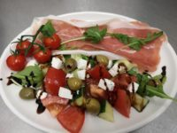 A white platter on a white table with dressed salad, ham, olives & feta cheese