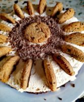A close up of a round cheesecake topped with chocolate shavings & cookies