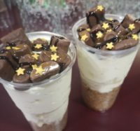 Plastic glasses containing cheesecake & cream topped with chocolate pieces & star shaped sprinkles