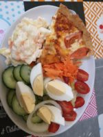 A white platter on a patterned tablecloth, with quiche, colslaw, salad & boiled eggs