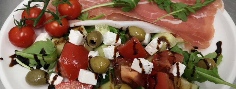 A close up of a salad platter with ham, olives & feta cheese