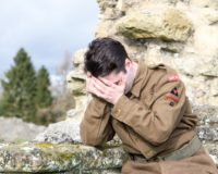 A white man wearing WW2 British Army uniform holds his head in his hands
