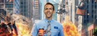 A picture of Guy (Ryan Reynolds) with a broad smile wearing a blue suit, striped tie and name badge. In the background amongst tall city buildings explosions are going off, giant fire balls and helicopters can be seen reminiscent of a computer game. A soldier fires a bullet, and there's an over turned car. Guy holds a coffee cup - a bullet has just shot through it and coffee is spilling out.