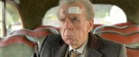 A still from the film. Tom (Timothy Spall) is sitting alone on a bus. A close up of his face, he has a large plaster on his forehead above his left eye.