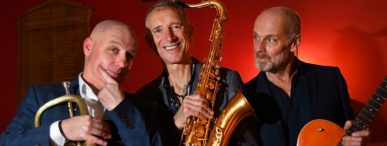 A picture of the three players in the trio. From left to right, Johnny Thirkell holds his trumpet, Snake Davis holds his Saxophone and Mark Creswell has his guitar. The three are relaxed and smiling.